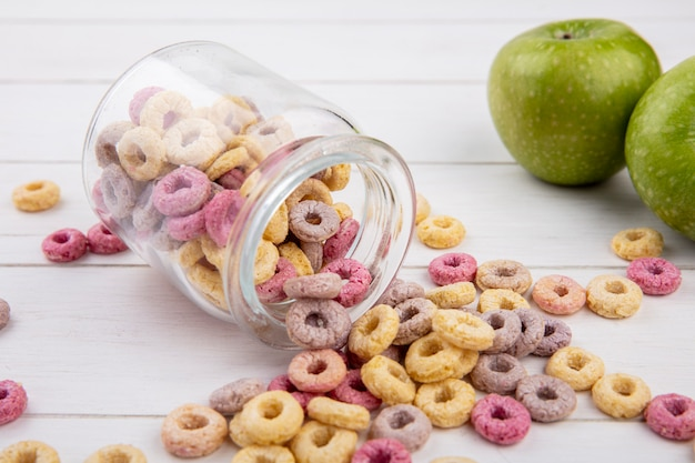 Top view of healthy loop and colored cereals on a glass jar with green apple on white surface