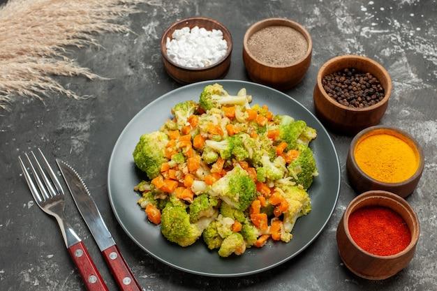 Vista dall'alto di un pasto sano con broccoli e carote su un piatto nero e spezie con forchetta e coltello