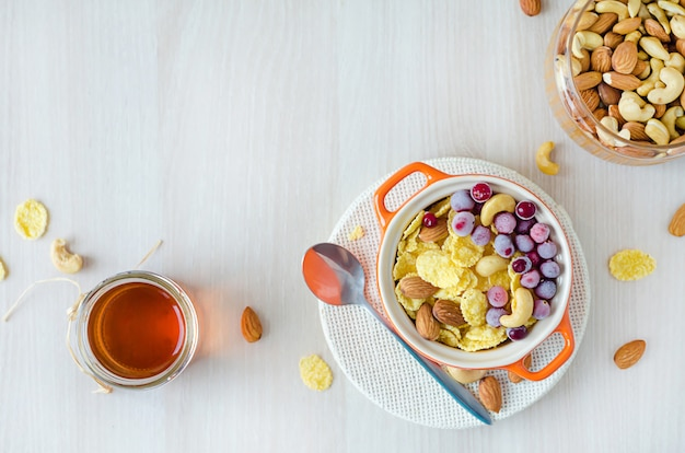 Top view of healthy nutritious breakfast for children and adults on wooden, copy space. corn flakes with honey, berries, cranberries, nuts, cashews, almonds.