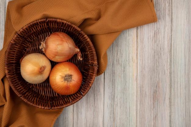 Vista dall'alto di cipolle sane su un secchio su un panno su una parete di legno grigia con spazio di copia