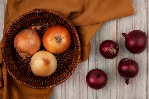 Vista dall'alto di cipolle sane su un secchio su un panno con cipolle rosse isolato su una superficie di legno grigia