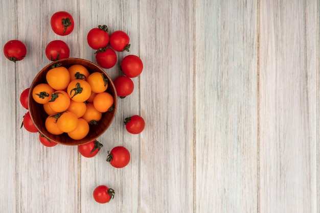 Top view of healthy orange tomatoes on a wooden bowl with red tomatoes isolated on a grey wooden surface with copy space