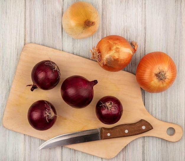 Vista dall'alto di cipolle rosse sane su una tavola di cucina in legno con coltello con cipolle gialle isolate su una parete di legno grigia
