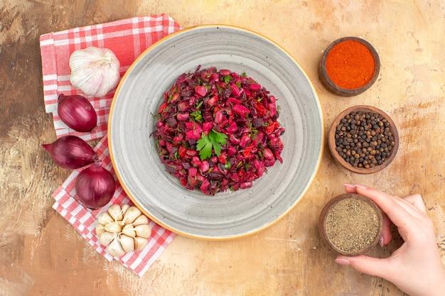회색 접시에 있는 건강한 붉은 샐러드 오른쪽에 검은 후추 가루가 있고 왼쪽에 붉은 양파 마늘 3개가 나무 배경에 있습니다.
