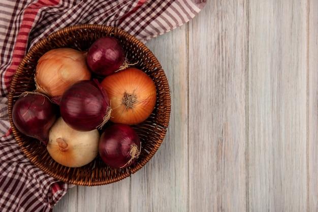 Vista dall'alto di cipolle rosse e bianche sane su un secchio su un panno controllato su una parete di legno grigia con spazio di copia