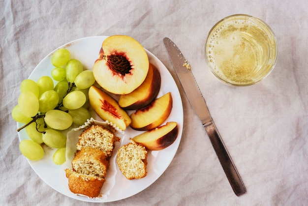 Top view of healthy refreshing brunch with fruits and glass of white wine over table cloth