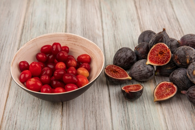 Top view of healthy ripe black mission figs with cornelian cherries on a bowl on a grey wooden wall