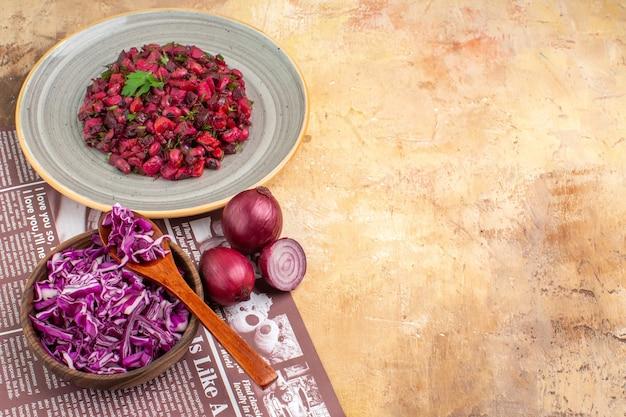 テキスト用の空きスペースがある木製のテーブルの上に赤い刻んだキャベツとタマネギのボウルで作られたパセリの葉で身を包んだトップビューの健康的なサラダ