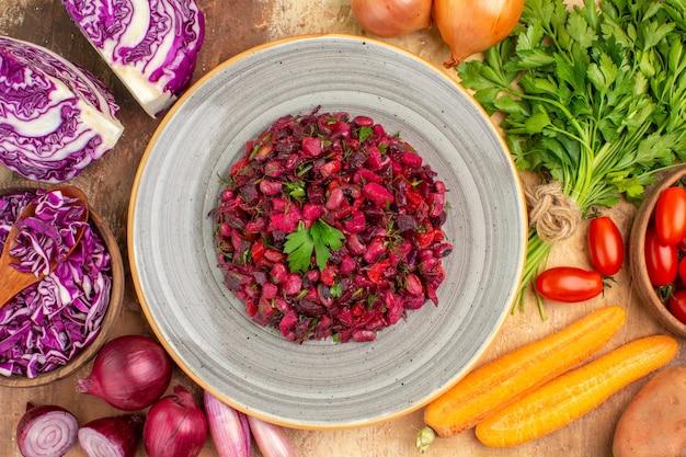 赤キャベツパセリの束ボウルのローマトマト、ニンジンポテト、タマネギなどの新鮮な野菜を木製のテーブルに置いたセラミックプレートのトップビューヘルシーサラダ