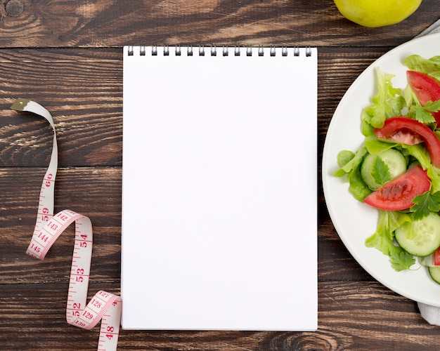 Top view healthy salad with notebook