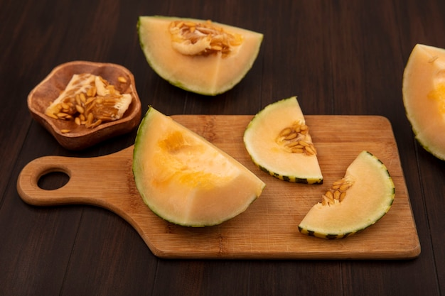 Top view of healthy slices of cantaloupe melon on a wooden kitchen board with melon seeds on a wooden bowl on a wooden wall