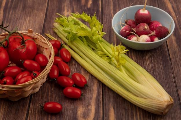 Vista dall'alto di pomodori sani su un secchio con ravanelli su una ciotola con sedano isolato su una parete in legno