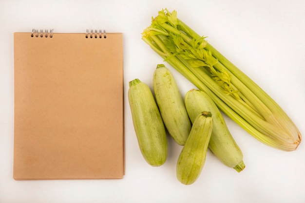 Top view of healthy vegetables such as celery and zucchinis isolated on a white background with copy space