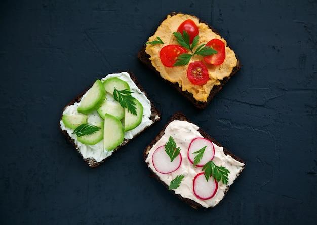 Вид сверху здоровые вегетарианские тосты из ржаного хлеба с творогом, хумусом, авокадо, редисом и помидорами на черной поверхности