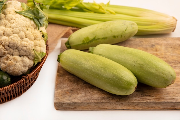 Top view of healthy zucchinis isolated on a wooden kitchen board with cauliflower on a bucket with celery isolated on a white wall