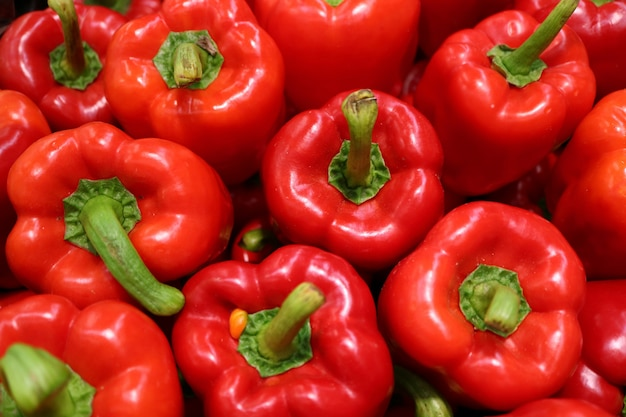 Top view of heap of fresh ripe red bell peppers with green stem