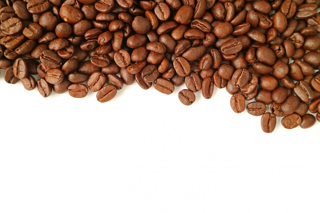 Top view of heap of roasted coffee beans isolated on white background