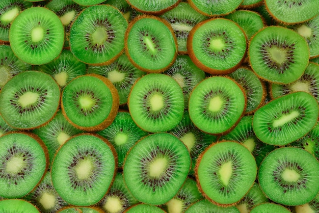 Top view of heap of sliced kiwi as textured background.