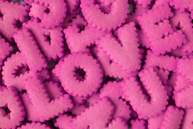 Top view of heap of vivid pink alphabet shaped biscuits spelling the word i love u