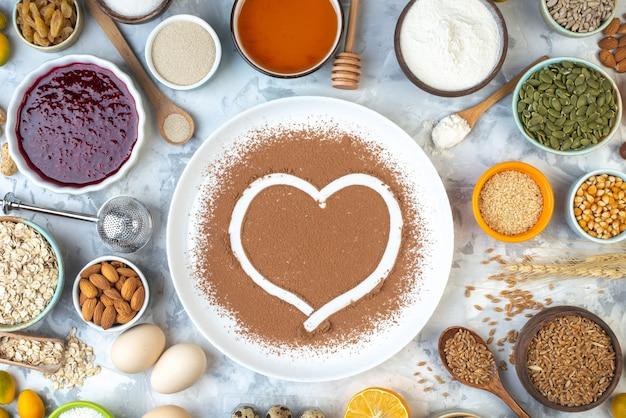 Отпечаток сердца в порошке какао на белых тарелках с другими продуктами на столе, вид сверху