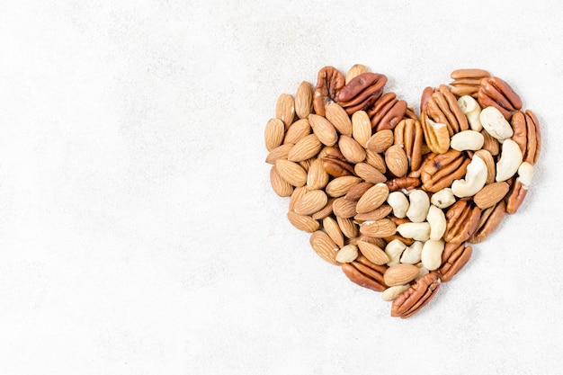 Top view of heart made of walnuts and almonds and copy space