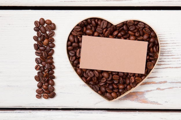 Top view heart shape made of beans and blank paper for your text. love for coffee. white wood background.