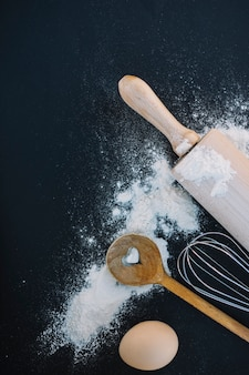 Top view of heart shape spoon; whisk; flour; egg and rolling pin on black background