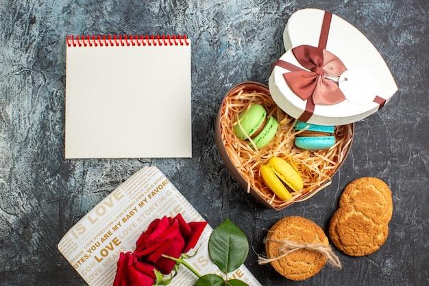 Vista dall'alto di una bellissima confezione regalo a forma di cuore con deliziosi macarons e biscotti, quaderno a spirale con rose rosse su sfondo scuro ghiacciato