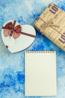 Вид сверху коробка в форме сердца подарочная спираль блокнот на синем фоне