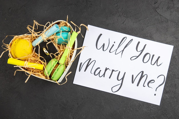 마카롱이 감긴 스티커 메모가 있는 위쪽 보기 하트 모양의 상자 어두운 배경에 종이에 쓰여진 나와 결혼해 줄래
