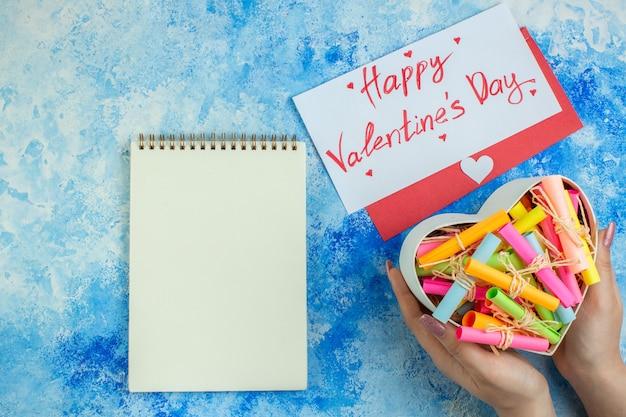 Вид сверху коробка в форме сердца со свитком с бумагами с пожеланиями в женских руках, тетрадное письмо и конверт на синем фоне