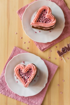 Top view of heart-shaped cake slices on wooden background