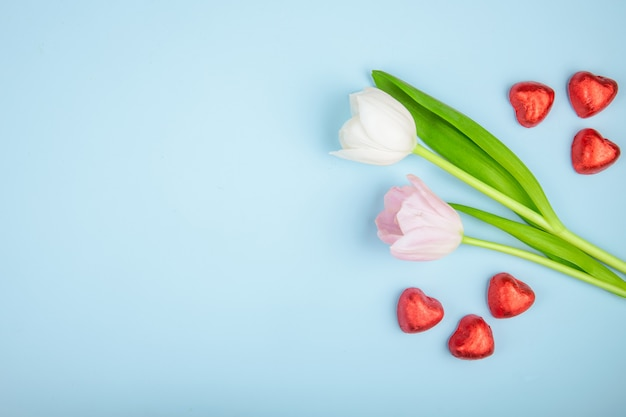 Top view of heart shaped chocolate candies in red foil with pink color tulips on blue table with copy space