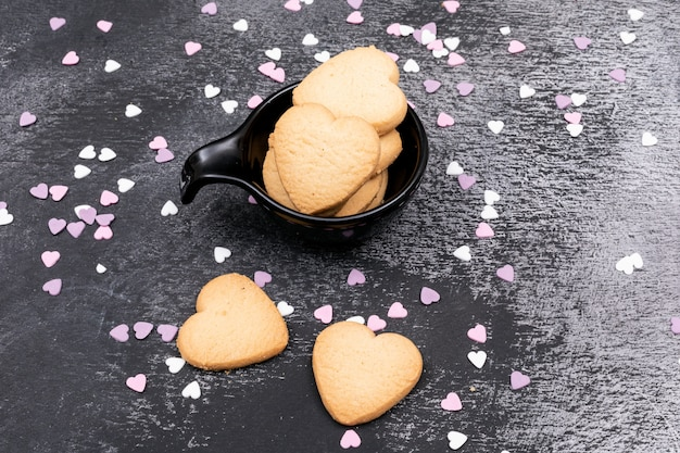 Top view heart shaped cookies on dark surface