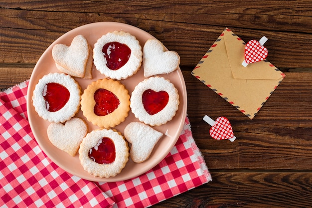 Top view of heart-shaped cookies on plate with jam