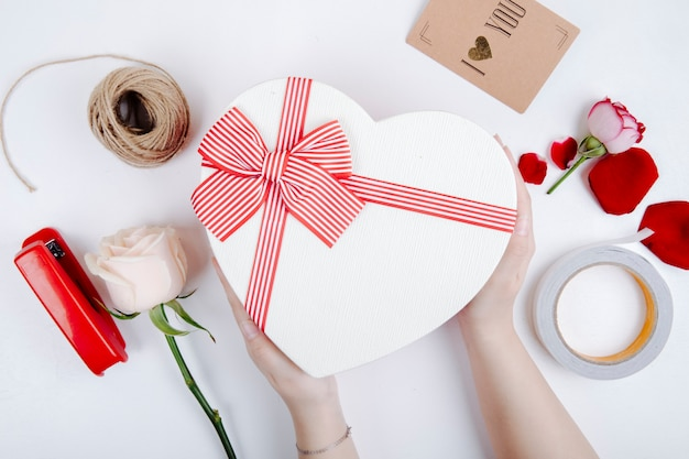 Top view of a heart shaped gift box with a bow and white color rose and stapler with rope and postcard on white background