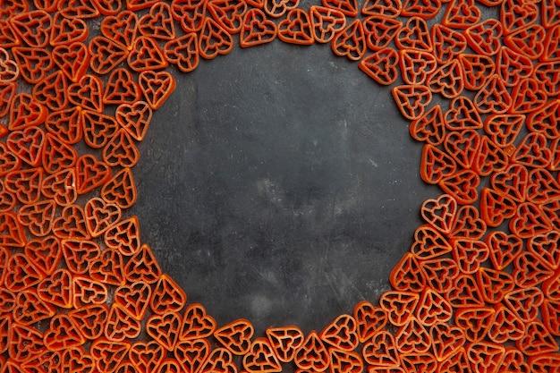 Vista dall'alto pasta italiana a forma di cuore sul tavolo scuro ovale posto vuoto