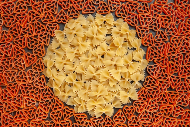 Top view heart shaped italian pasta and farfalles on dark table