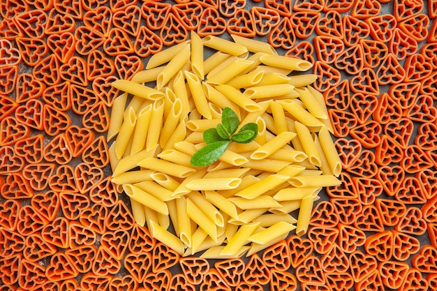 Top view heart shaped italian pasta and penne on dark table
