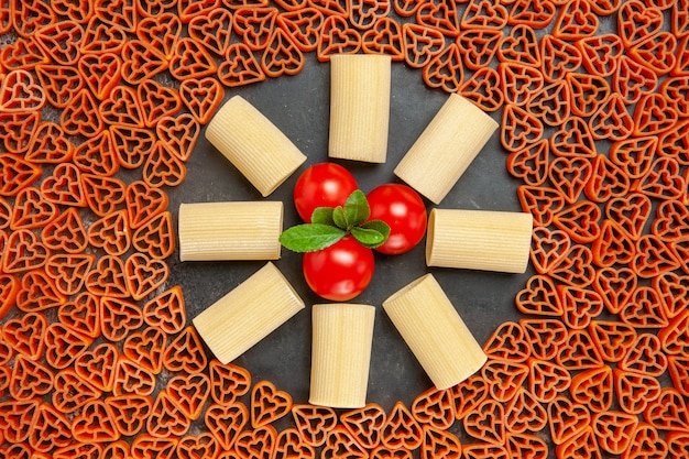 Top view heart shaped italian pasta rigatoni and cherry tomatoes on dark table