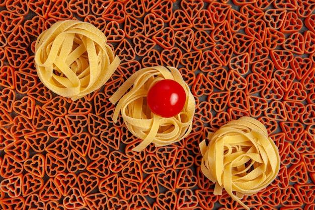 Top view heart shaped italian pasta tagliatelle and cherry tomato on dark table