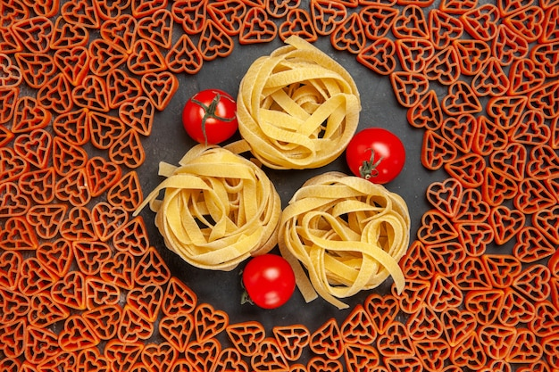 Top view heart shaped italian pasta tagliatelles and cherry tomatoes on empty place on dark table