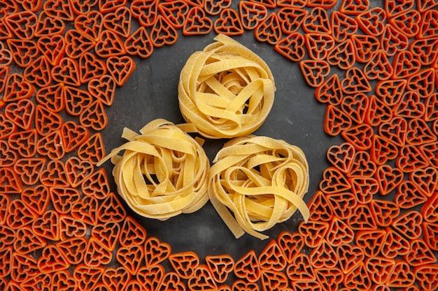 Top view heart shaped italian pasta tagliatelles on empty place on dark table