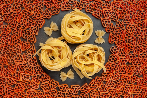Top view heart shaped italian pasta tagliatelles and farfalles on empty place on dark table