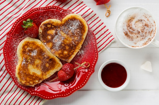 Top view of heart-shaped pancakes with strawberry