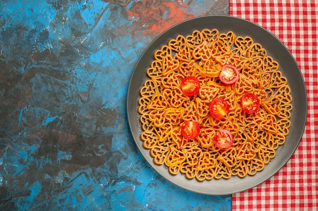 Vista dall'alto pasta a forma di cuore con pomodorini su piatto ovale scuro su tavolo blu copia posto