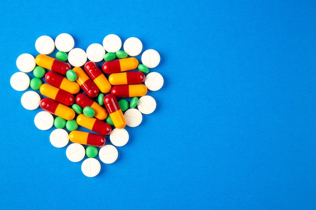Top view heart shaped pills different colored on blue background