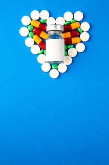 Top view heart shaped pills different colored with vaccine on blue background