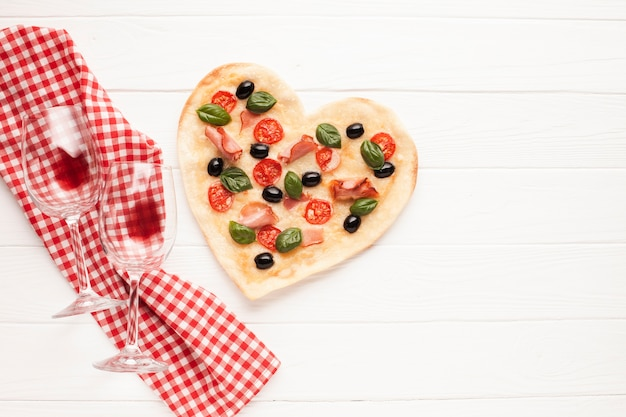 Top view heart shaped pizza on table with cloth