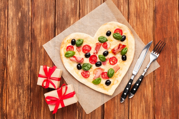 Top view heart shaped pizza with gifts
